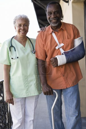 Photo for Portrait of an African American disabled patient standing with doctor in hospital - Royalty Free Image