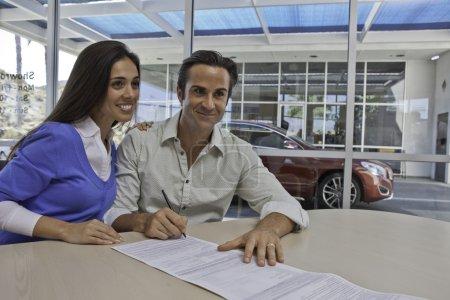 Photo pour Couple de signer des documents pour voiture neuve - image libre de droit