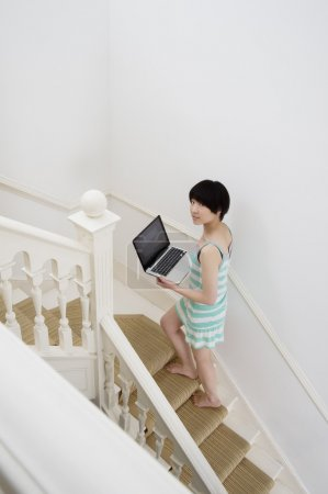 Full length of young woman with laptop walking up stairway