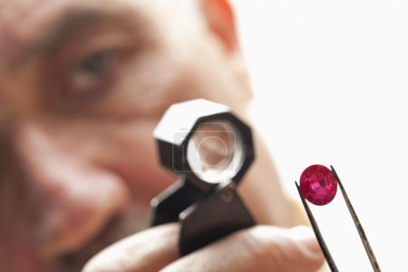 Close up of gemstone with jeweler looking through magnifying glass