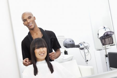 Hairstylist with female customer at beauty salon