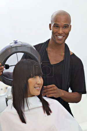 Asian woman getting herself groomed at hair salon