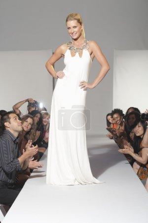 Photo pour Longueur totale d'un mannequin en robe blanche posant sur piste entouré par le public - image libre de droit