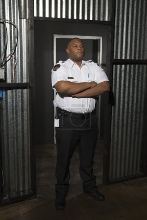 Security Guard Standing With Arms Crossed On Duty