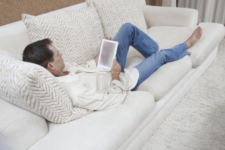 Photo for Full length of mature man in casual wear looking at digital tablet while reclining on sofa at home - Royalty Free Image