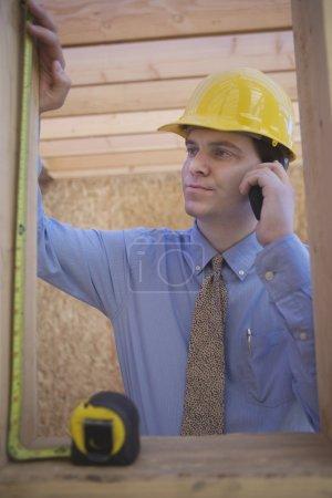 Photo pour Jeune architecte mesurant une poutre en bois lors de l'utilisation d'un téléphone portable sur le chantier - image libre de droit