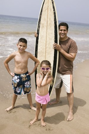 Man holding surfboard with children