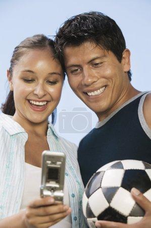 Photo pour Jeune couple à l'aide de téléphone mobile homme tenant le ballon de soccer - image libre de droit