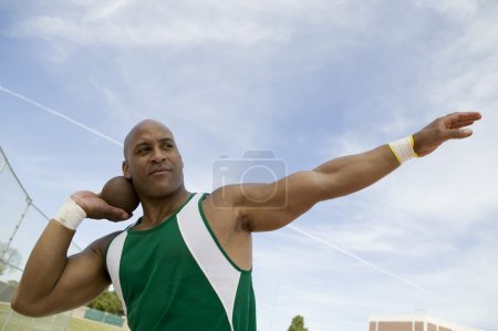 Photo for Closeup of a shot putter preparing to toss shot put against the sky - Royalty Free Image