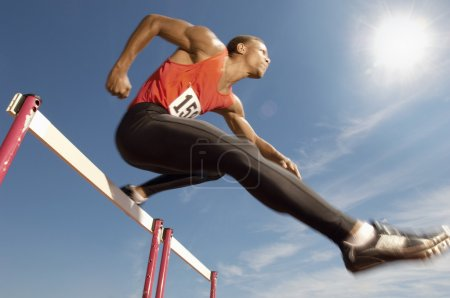 Athlete jumping over a hurdles
