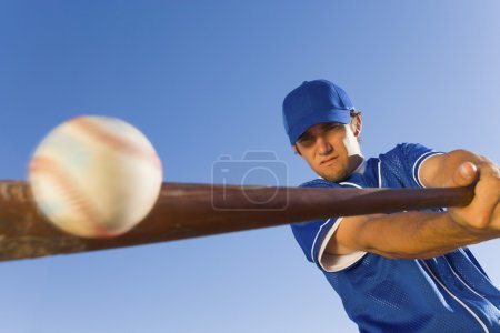Photo for Baseball player hitting ball with bat low angle view - Royalty Free Image