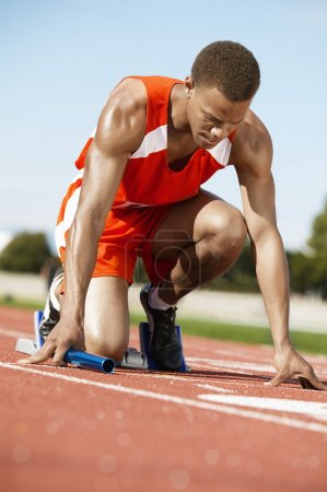 Photo for Male runner at starting block  on racing track - Royalty Free Image