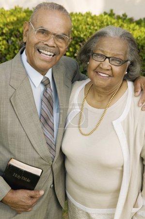 Photo pour Souriant couple chrétien âgé dans jardin tenant le portrait de la bible - image libre de droit