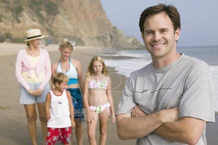 Man on beach with family