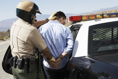 Police officer guiding apprehended man into police...