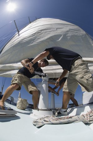 Sailors operating windlass on yacht