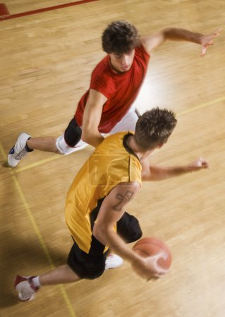 Photo pour Vue en angle élevé de jeunes hommes jouant au basket-ball sur le terrain intérieur - image libre de droit