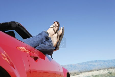 Woman lying in red convertible