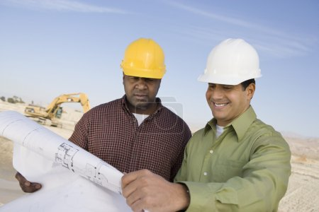 Photo for Two multiethnic construction workers with blueprints against the sky at site - Royalty Free Image