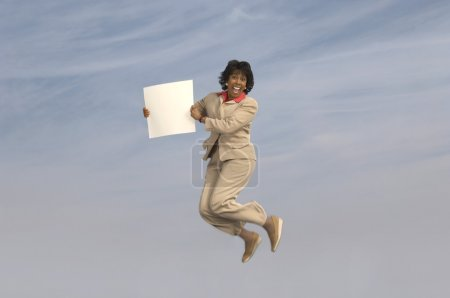 Businesswoman jumping with blank sign