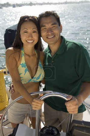 Happy Asian couple steering a sailboat