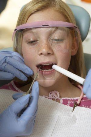 Girl having teeth examined