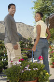 Couple pulling potted plants