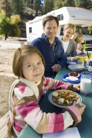 Photo for Girl eating at picnic table with family in campground - Royalty Free Image