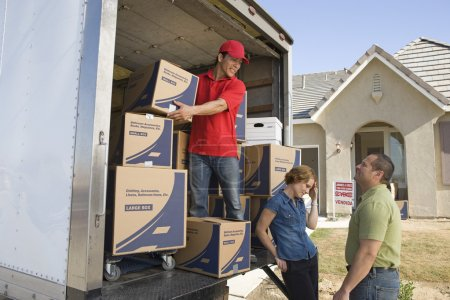 Photo for Delivery man and couple unloading moving boxes from truck into new house - Royalty Free Image