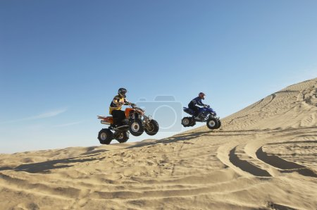 Men doing wheelies on quad bikes