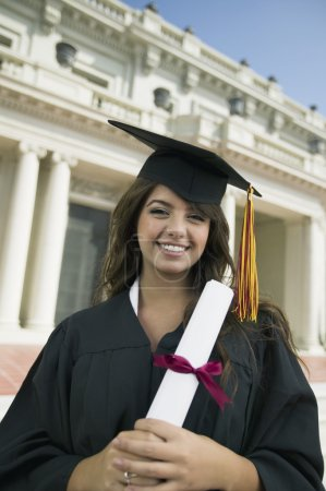 Photo for Graduate holding diploma outside university - Royalty Free Image