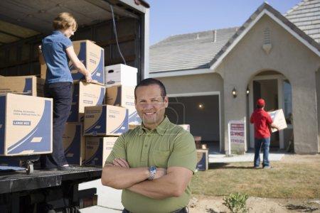 Photo pour Homme debout devant le fourgon de livraison et la nouvelle maison - image libre de droit