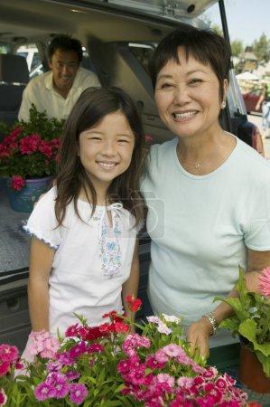 Photo pour Grand-mère et petite-fille de fleurs par l'arrière du portrait de suv - image libre de droit