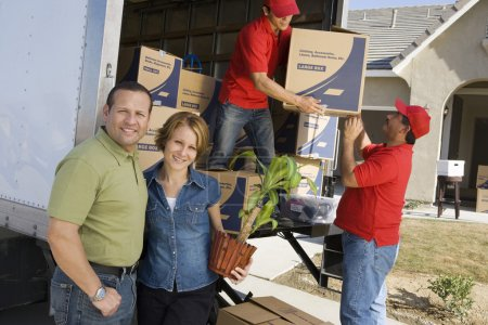 Photo for Happy couple with delivery men unloading moving boxes from truck into new house - Royalty Free Image