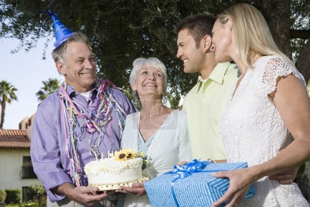 Couples with birthday gift and cake