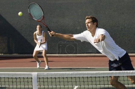 Photo pour Double mixte de tennis joueur atteignant pour boule - image libre de droit