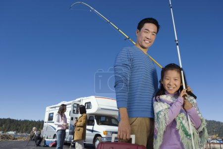 Father and daughter holding fishing poles