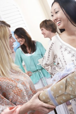 Woman giving a gift to pregnant female