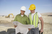 Construction workers reading blueprints