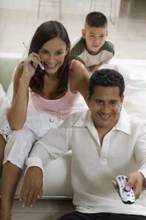 Family sitting on sofa watching TV