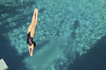 Female diver diving in pool