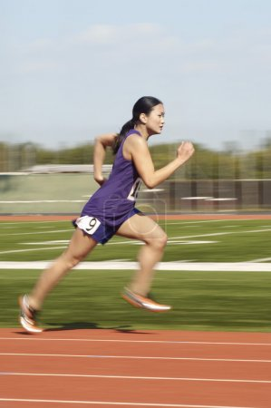 Photo for Side view of Asian female athlete running on race track - Royalty Free Image