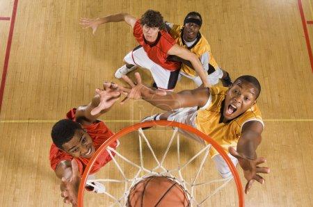 Photo pour Vue d'angle élevé de basketteur tremper basketball au cerceau - image libre de droit