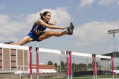female athlete jumping over a hurdles