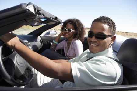 Couple driving convertible on desert road