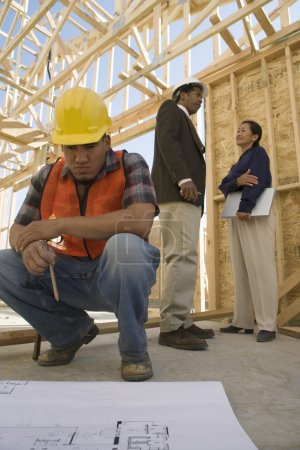 Construction worker looking at blueprints