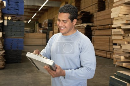 Man checking lumber in warehouse