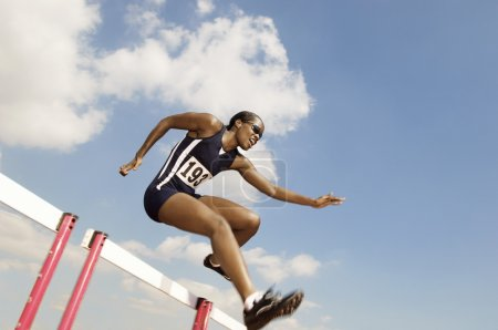 Photo for Female athlete jumping hurdle - Royalty Free Image