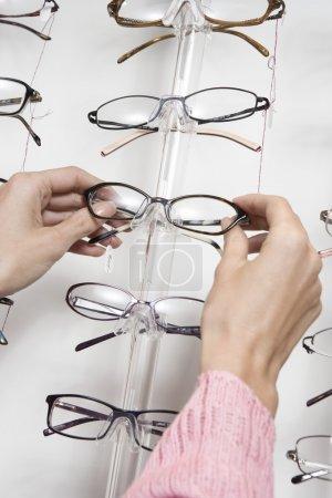 Hands choosing eyeglasses