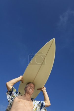 Surfer carrying surfboard